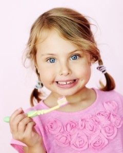 Child happily brushing her teeth